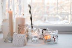 与光的蜡烛 在窗台的构成 与蜡烛和芳香棍子的逗人喜爱的家庭装饰 平静放松,拔去, 免版税库存照片