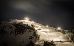 与光的滑雪倾斜在晚上 库存图片