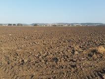 与光秃的土壤的被犁的领域 免版税库存图片