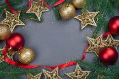 与光诗歌选的红色和金黄圣诞装饰玩具球和星背景  库存图片