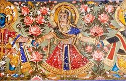 与克里希纳阁下的妇女跳舞在壁画的花的 库存图片