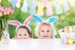 与兔宝宝耳朵和鸡蛋的孩子在复活节彩蛋寻找 免版税图库摄影