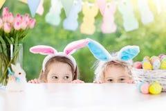 与兔宝宝耳朵和鸡蛋的孩子在复活节彩蛋寻找 库存图片