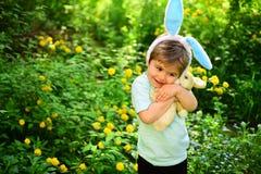 与兔宝宝耳朵的兔子孩子 野兔玩具 蛋狩猎春天假日 爱复活节 家庭假日 小男孩孩子以绿色 免版税图库摄影