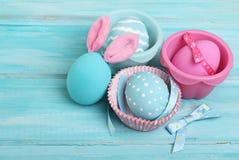 与兔宝宝耳朵的复活节桃红色和蓝色鸡蛋 免版税库存照片