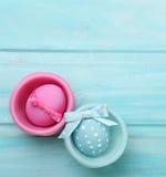 与兔宝宝耳朵的复活节桃红色和蓝色鸡蛋 免版税库存图片