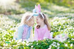 与兔宝宝耳朵的孩子在复活节彩蛋寻找 库存图片