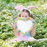 与兔宝宝耳朵的孩子在复活节彩蛋寻找 图库摄影