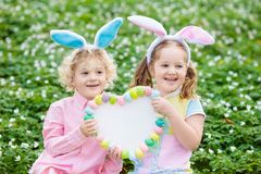 与兔宝宝耳朵的孩子在复活节彩蛋寻找 库存照片