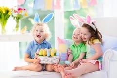 与兔宝宝耳朵的孩子在复活节彩蛋寻找 免版税库存图片