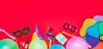 与党工具和装饰- baloons,滑稽的狂欢节面具,欢乐闪亮金属片的明亮的红色欢乐背景 生日快乐gree 库存图片