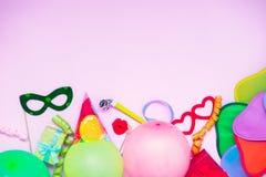与党工具和装饰- baloons,滑稽的狂欢节面具,欢乐闪亮金属片的浅粉红色的欢乐背景 生日快乐gree 免版税库存图片