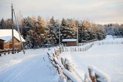 与全部的冬天雪在俄国村庄,在日落光,俄罗斯的农村街道 库存图片