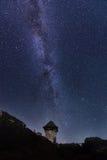 与全部的夜满天星斗的天空发光的星和五颜六色的银河在Perseid流星雨期间在中世纪城堡塔  免版税库存照片