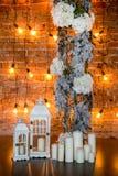 与八仙花属灌木、蜡烛和电灯泡的具球果分支在砖背景,垂直的框架 免版税库存图片