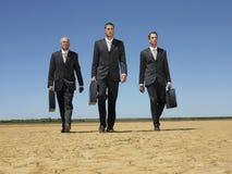 与公文包的商人走在沙漠的 免版税库存照片