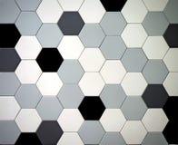 与六角瓦片的现代铺磁砖的地板 是黑,白色,轻和深灰的任意地被安排的颜色 图库摄影