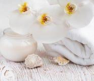 与兰花和毛巾的润湿的奶油 库存照片