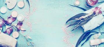 与兰花花和身体关心的温泉设置和在破旧的别致的绿松石背景,顶视图,横幅的化妆用品工具 免版税库存图片