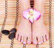 与兰花花的美好的被修剪的女性赤脚和在竹席子的温泉石头 免版税库存照片