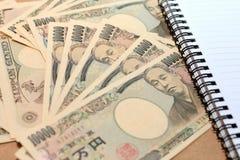 与关于日元货币的10000日元笔记与笔记本 免版税库存图片