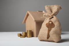 与关键标志的小袋子和在房子的工艺形象的背景的金币 出租价格,买庄园保险 库存照片