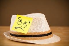 与兴高采烈的面孔的便条纸在帽子sticked 库存图片