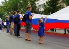 与其他活动家一起的小女孩在俄罗斯的独立日拿着一面大俄国旗子在伏尔加格勒 免版税库存照片