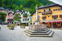 与典型的五颜六色的房子的宗教纪念碑在Hallstatt 库存图片