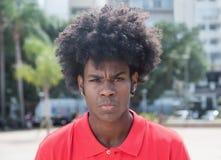 与典型的非洲的发型的恼怒的非洲年轻成人 库存照片