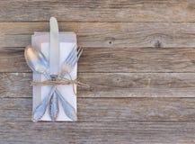 与典雅的利器的在木桌背景的餐位餐具和餐巾 免版税图库摄影