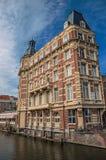 与典雅的装饰的老砖瓦房沿运河、自行车和晴朗的蓝天在阿姆斯特丹 图库摄影