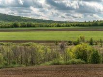 与农业领域和绿地的风景在与多云天空的一好日子 库存照片