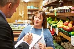 与农厂商店女性店主的银行经理会议  库存照片