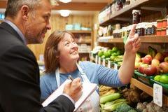 与农厂商店女性店主的银行经理会议  免版税库存图片