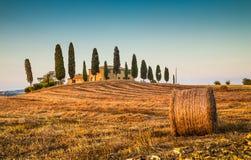 与农厂房子的托斯卡纳风景日落的, Val d'Orcia,意大利 免版税库存照片