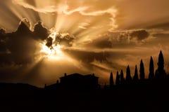 与农夫房子的托斯卡纳著名柏树与光芒的日落的点燃 库存图片