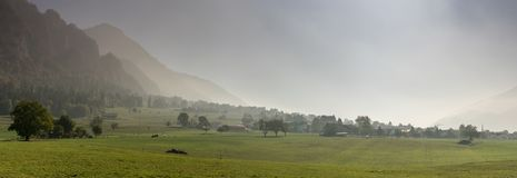 与农田的农村瑞士乡下风景和迷雾山脉和森林在晚秋天 库存照片