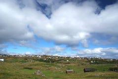 与农舍的国家风景在多云天空下在Torshavn,丹麦 美好的横向视图 丘陵地带与 图库摄影