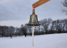 与冬天斯诺伊领域的金属响铃在背景中 免版税库存图片