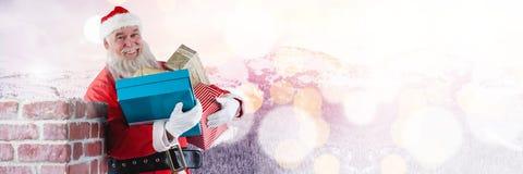 与冬天风景和礼物的圣诞老人由烟囱 库存图片