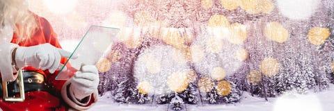 与冬天风景的圣诞老人与玻璃片剂 免版税图库摄影
