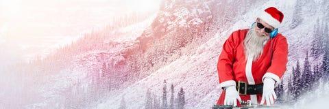 与冬天风景的圣诞老人在有DJ耳机的甲板 库存图片