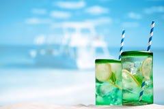 与冰、兰姆酒、柠檬和薄菏的鸡尾酒在海滩的一块玻璃 库存照片