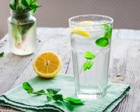 与冰、柠檬切片和新鲜薄荷的柠檬水在玻璃 库存图片