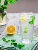 与冰、柠檬切片和新鲜薄荷的柠檬水在玻璃 库存照片