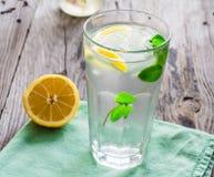 与冰、柠檬切片和新鲜薄荷的柠檬水在玻璃 免版税库存照片