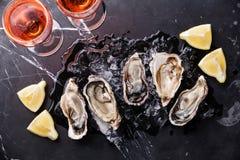 与冰、柠檬和玫瑰酒红色的被打开的牡蛎 免版税库存照片
