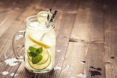 与冰、柠檬和薄荷叶的冷的新鲜的Mojito鸡尾酒柠檬水在金属螺盖玻璃瓶 库存照片