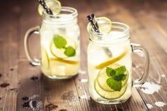 与冰、柠檬和薄荷叶的冷的新鲜的Mojito鸡尾酒柠檬水在金属螺盖玻璃瓶 免版税库存照片